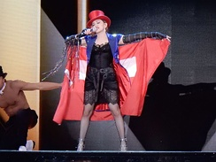 Madonna wearing a red flag around herself, and a red tophat singing onstage.