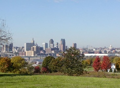 St. Paul, showing barges on the Mississippi River, the Capitol dome, and Minneapolis's skyline in the far background (right of St. Paul). In the lower right is a typical nineteenth century home. Taken from Indian Mounds Park.