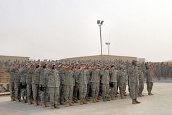 Formation of Airmen deployed to the 387th Air Expeditionary Group lead the 386th Air Expeditionary Wing as they render a salute during a Memorial Day ceremony 26 May 2008 at an air base in the Persian Gulf Region. During the ceremony, a 21-gun salute was conducted along with a laying of a wreath to honor the men and women who have died in military service.