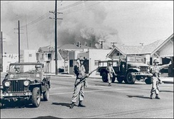 Soldiers of the California's 40th Armored Division direct traffic away from an area of South Central Los Angeles burning during the Watts riot.