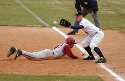 A first baseman receives a pickoff throw, as the runner dives back to first base.