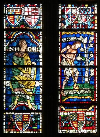 Two panels of lively figures, Seth and Adam from the 12th-century Ancestors of Christ, Canterbury Cathedral, now set into a Perpendicular Gothic window with panels of many different dates.