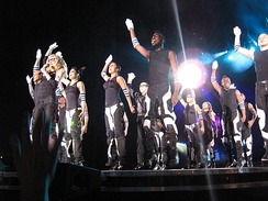 Left profile of a group of people jumping onstage with their right hand stretched up. They are wearing black tops and black-and-white striped pants and wrist bands. They have white gloves on their right hand. They are illuminated by white light from above.