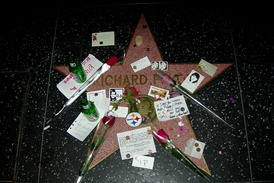 Richard Pryor's star at the Hollywood Walk of Fame covered with flowers, beer bottles, fan letters, etc.