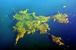 September 2005 aerial view of Sark. North is to the lower left, Little Sark toward the upper right and Brecqhou at bottom right.