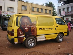 An advertisement for a mobile phone carrier on a van in Kampala.