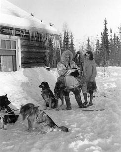 This 1940 Census publicity photo shows a census worker in Fairbanks, Alaska. The dog musher remains out of earshot to maintain confidentiality.