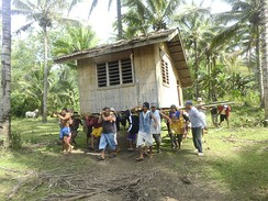 "Community members practicing ""bayanihan"", working together to move a house to new location."