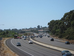 Under clear skies, vehicles travel on the freeway. Brush surrounds the freeway, but buildings can be seen in the distance.