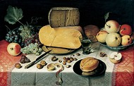 Still life with fruits, nuts, and large wheels of cheese.