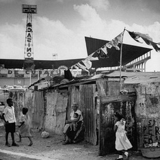 Slum (bohio) dwellings in Havana, Cuba in 1954, just outside Havana baseball stadium. In the background is advertising for a nearby casino.