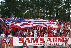 U.S. soccer fans, dressed in red, cheer in bleachers as they hold a large U.S. flag over themselves at a soccer match.