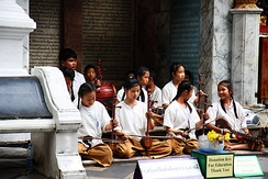 Schoolgirls and boys playing khrueang sai in front of a temple