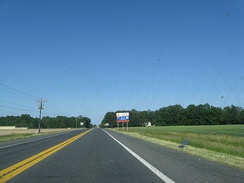 A two-lane road passing through farm fields. A blue and white sign on the right indicates an ongoing construction project on US 113.