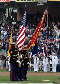 "A U.S. Marine color guard dips the U.S. Marine Corps flag for a playing of ""The Star-Spangled Banner"" in April 2005."