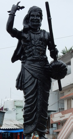 A black statue of an aged man holding a tambura in his hand