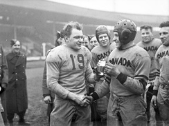 In 1944, Canadian and American teams played an exhibition game at White City Stadium in London, United Kingdom. The Canadian Mustangs defeated the U.S. Pirates 16–6. Here, captains Frank Dombrowski (left) of the United States and W. Drinkwater of Canada shake hands.