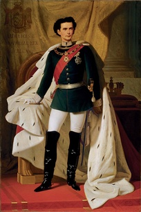 A young man in a dark military jacket, jodhpurs, long boots, and a voluminous ermine robe. He wears a sword at his side, a sash, a chain and a large star. Mainly hidden by his robe is a throne and behind that is a curtain with a crest with Ludwig's name and title in Latin. To one side a cushion holding a crown sits on a table.
