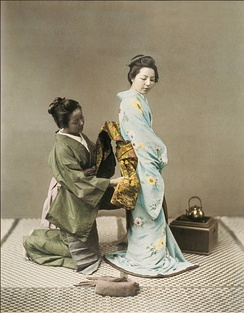 A Japanese woman tying the obi of a geisha in the 1890s.