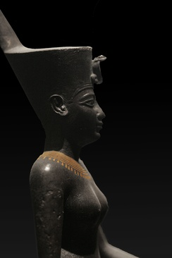 A statue of the Egyptian war goddess Neith wearing the Deshret crown of northern (lower) Egypt, which bears the cobra of Wadjet.