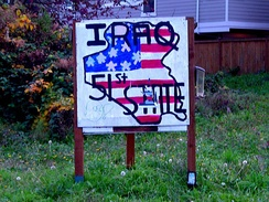 A resident of Seattle, Washington, through a homemade sign, facetiously declares that the Republic of Iraq is the 51st U.S. state.