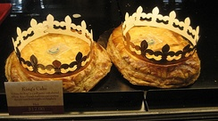 "King cakes of the type locally called ""French style"" on display at the chain bakery/restaurant ""La Madeline"" branch in Carrollton, New Orleans. They come with cardboard ""crowns"" to be worn by whoever gets the slice with the token and becomes monarch of the event."