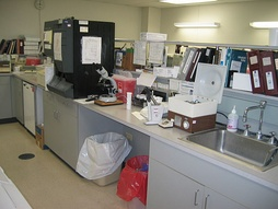 Laboratory equipment for hematology (black analyser) and urinalysis (left of the open centrifuge).