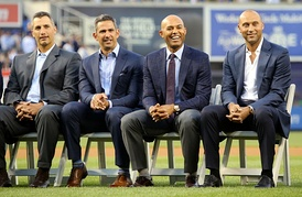 Andy Pettitte, Jorge Posada, Mariano Rivera, and Derek Jeter dressed in suits and seated in chairs on a baseball field.