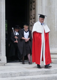 Lord Eatwell, in academic dress, leaving the Senate House