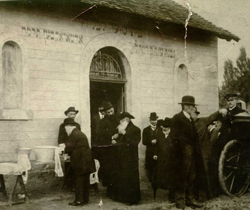 "Visitors in the Orthodox Jewish cemetery in Budapest, circa 1920 (the word ""Orthodox"" is painted on the wall, second to the left). Traditionalist Jews in Hungary were the first anywhere to form an independent Orthodox organization in 1871."
