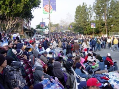 "Spectators gather before the 2004 Rose Parade: some pay for seats in stands; others spend the night to ""reserve"" a free spot on the sidewalks."