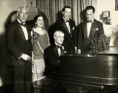 Birthday party honoring French pianist Maurice Ravel in 1928. From left to right: conductor Oskar Fried, singer Éva Gauthier, Ravel (at piano), composer-conductor Manoah Leide-Tedesco, and composer George Gershwin.