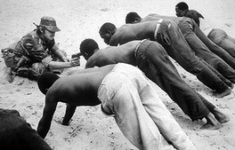 White soldier interrogates Rhodesian villagers about insurgent activity in late 1977. This photograph became one of the most enduring images of the bush war.