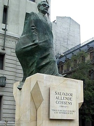 Statue of Allende in front of the Palacio de la Moneda. A portion of the statue's drapery, shown worn as a cape, is the national flag of Chile.