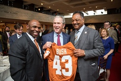 (L–R) Charlie Strong, Texas Longhorns head football coach, George W. Bush and Reverend Jesse Jackson hold up a Texas Longhorns football jersey at the LBJ Presidential Library in 2014