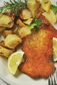 "A traditional ""Cotoletta alla milanese (Milanese-style cutlet)"" served with potatoes."