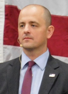 A man wearing a suit and a headset microphone, in front of the red and white stripes of a U.S. flag
