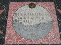 "Moon Landing monument, with square pink terrazzo surround (not the usual charcoal color), with light gray terrazzo Moon disk showing TV emblem at top and the brass lettering ""Neil A. Armstrong, Edwin E. Aldrin and Michael Collins, 7/20/69, Apollo XI"""