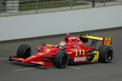 Photograph of Wilson driving a red Dallara-Honda car on a race track