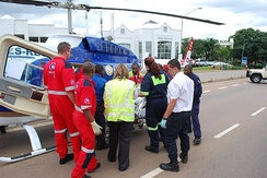 Various ambulance crews help to load a patient into an air ambulance in Pretoria
