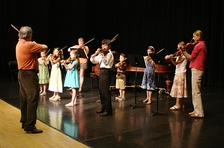 A group of Suzuki method students performing on violin.