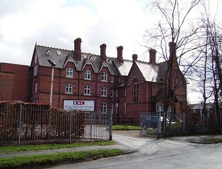 "A large brick building with a sign saying ""RNC""; a fence and some trees in the foreground."