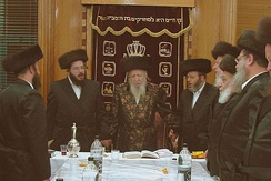 "The Bostoner Rebbe feert tish, lit. ""runs [a] table"" in his synagogue in Beitar Illit"