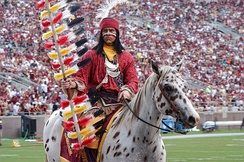 A brown and white spotted horse ridden by a sports mascot in modern-day Native American attire waving a flag stands on a sports field. More people are visible on the field, and a large crowd fills the stadium seating in the background.