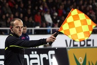 A man dressed in black. He is stretching his right arm forwards, holding a red and yellow chequered flag.