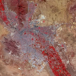 False-color satellite image of El Paso and Ciudad Juárez: Paved streets and buildings appear in varying shades of blue-gray, and red indicates vegetation