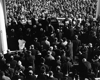 The Inauguration of John F. Kennedy as seen from behind. The few top hats in the crowd can be distinguished by the shininess of the hat's flat crown