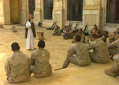 A Catholic chaplain ministers to American U.S. Marines and sailors in Tikrit, Iraq