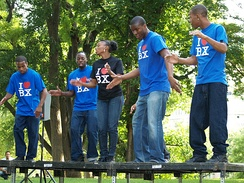 "The Bronx's P.L.A.Y.E.R.S. Club Steppers performing at the 2007 Fort Greene Park Summer Literary Festival in Brooklyn. (Note the T-shirts' inscription ""I ♥ BX"" [Bronx], echoing the ubiquitous slogan ""I ♥ NY"" [I Love New York] ).[138][139]"