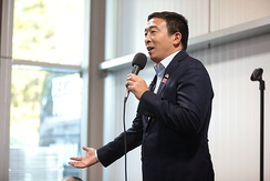 Yang holding a microphone while making a speech.